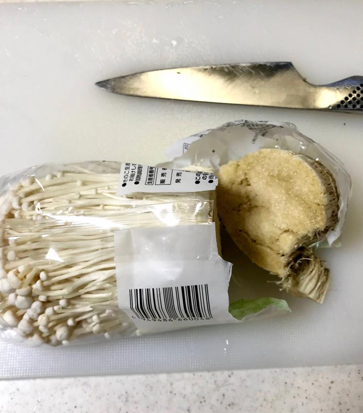 <p>1. えのき茸は、袋のまま根元の部分を切り落とす。</p>