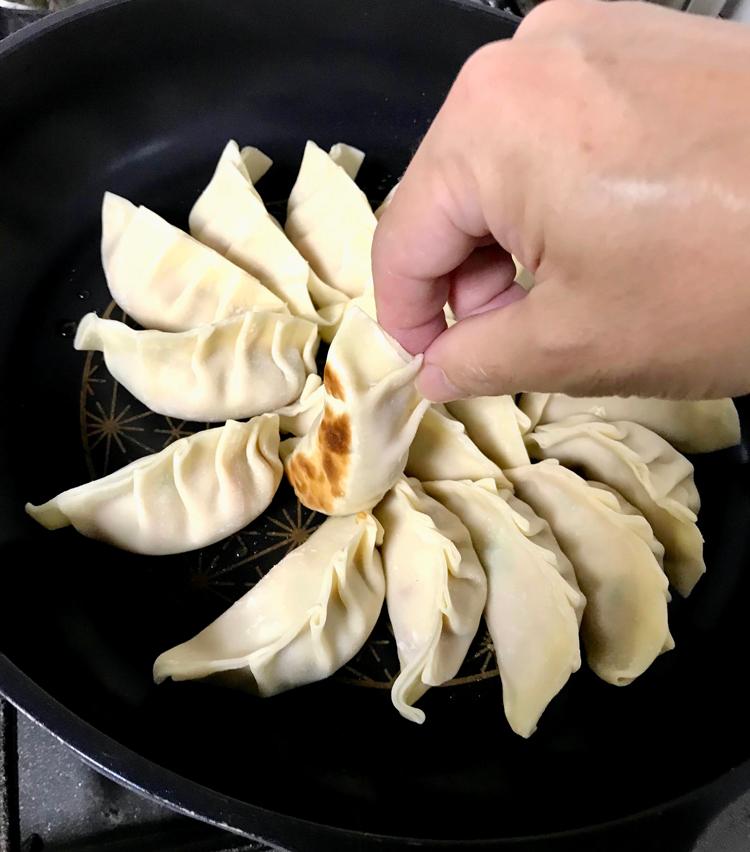 <p>10. 皮に軽く焼き目が付いたら、熱湯1カップを入れ、蓋をして蒸し焼きにする。3〜4分ほど経ったら蓋を開け、フライパンを回しながら水気を飛ばす。</p>