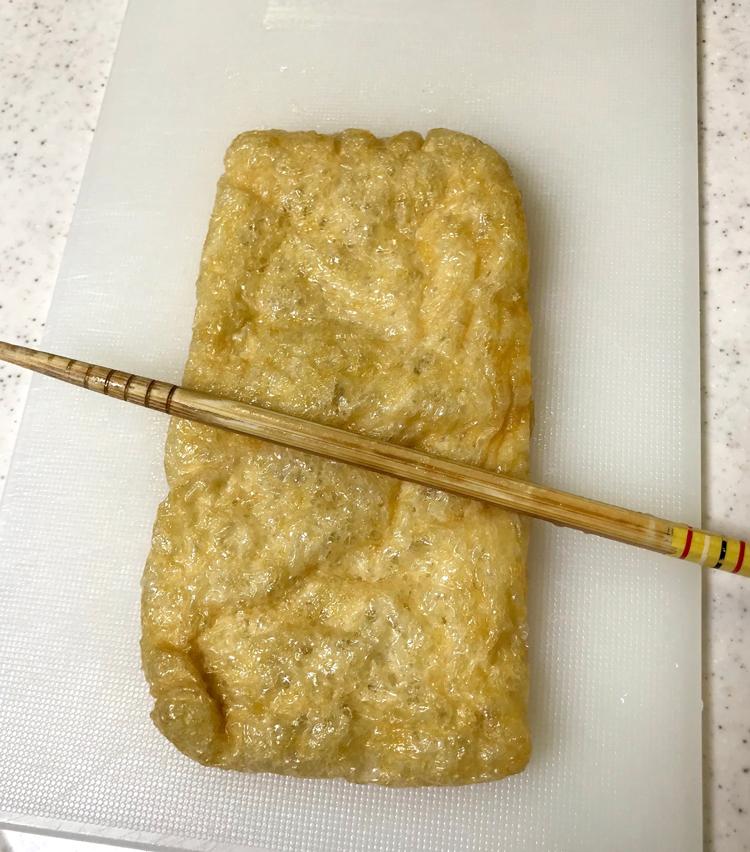 <p>1. 油揚げは箸を転がし、半分に切る。</p>