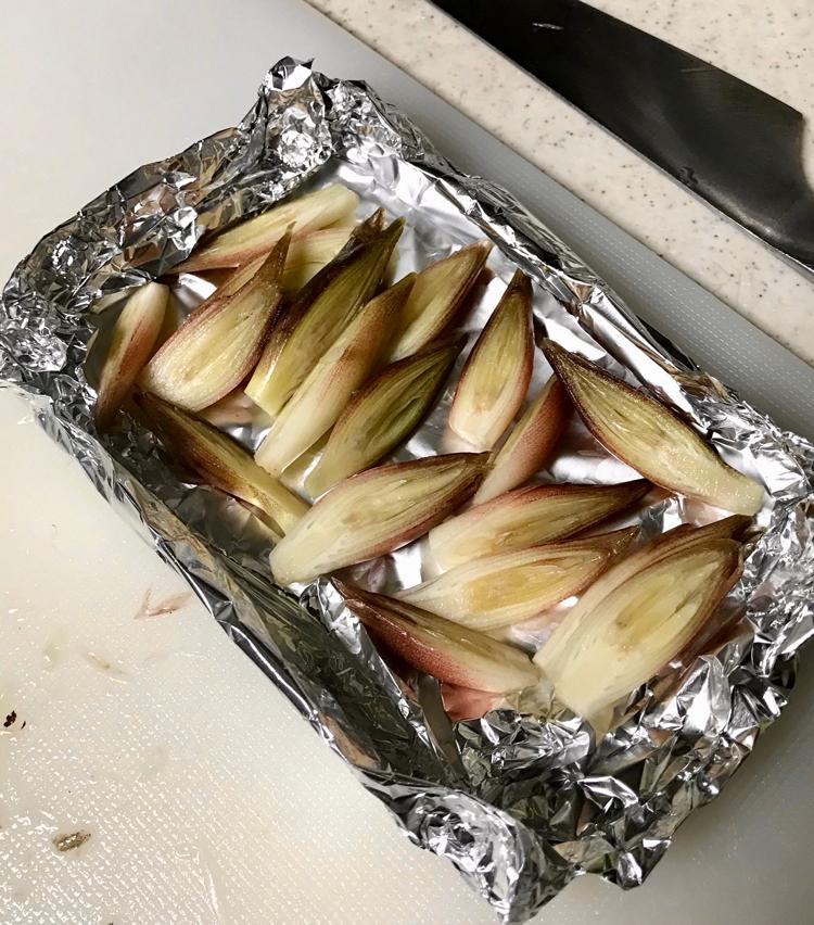 <p>8. 次に「秋茗荷の味噌焼き」。茗荷は縦に半分に切り、アルミホイルで作った皿に並べる。</p>