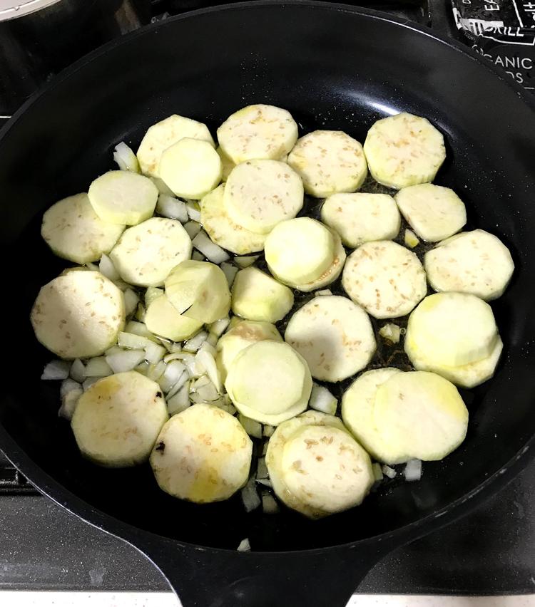 <p>4. フライパンにオリーブオイル大さじ1(分量外)を入れ、弱火にし、茄子、玉ねぎ、ニンニクを入れる。塩ひとつまみ(分量外)をし、全体に油が回ったら、白ワイン大さじ1を回し入れ、蓋をして蒸し焼きにする。</p>
